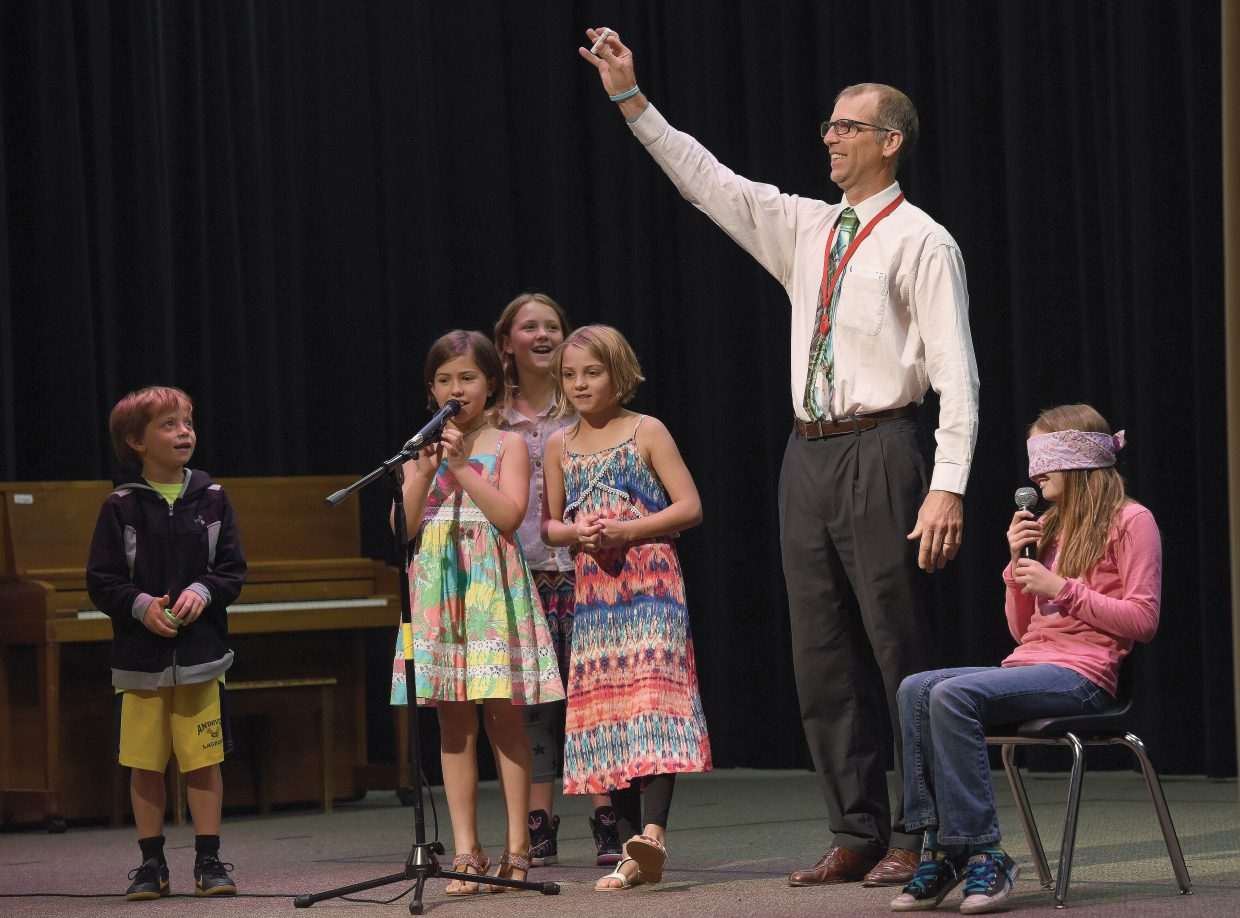 Soda Creek Elementary School fifth-grade teacher Andrew Miller holds up a ChapStick during a talent show skit Wednesday morning. The annual talent show marks the end of the school year for the school's students.