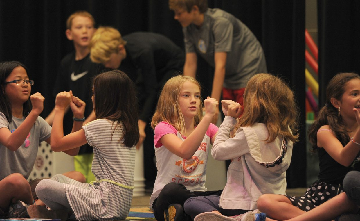Olivia Harlen bumps fists Wednesday with a classmate while performing as part of the Soda Creek Elementary School Talent Show .