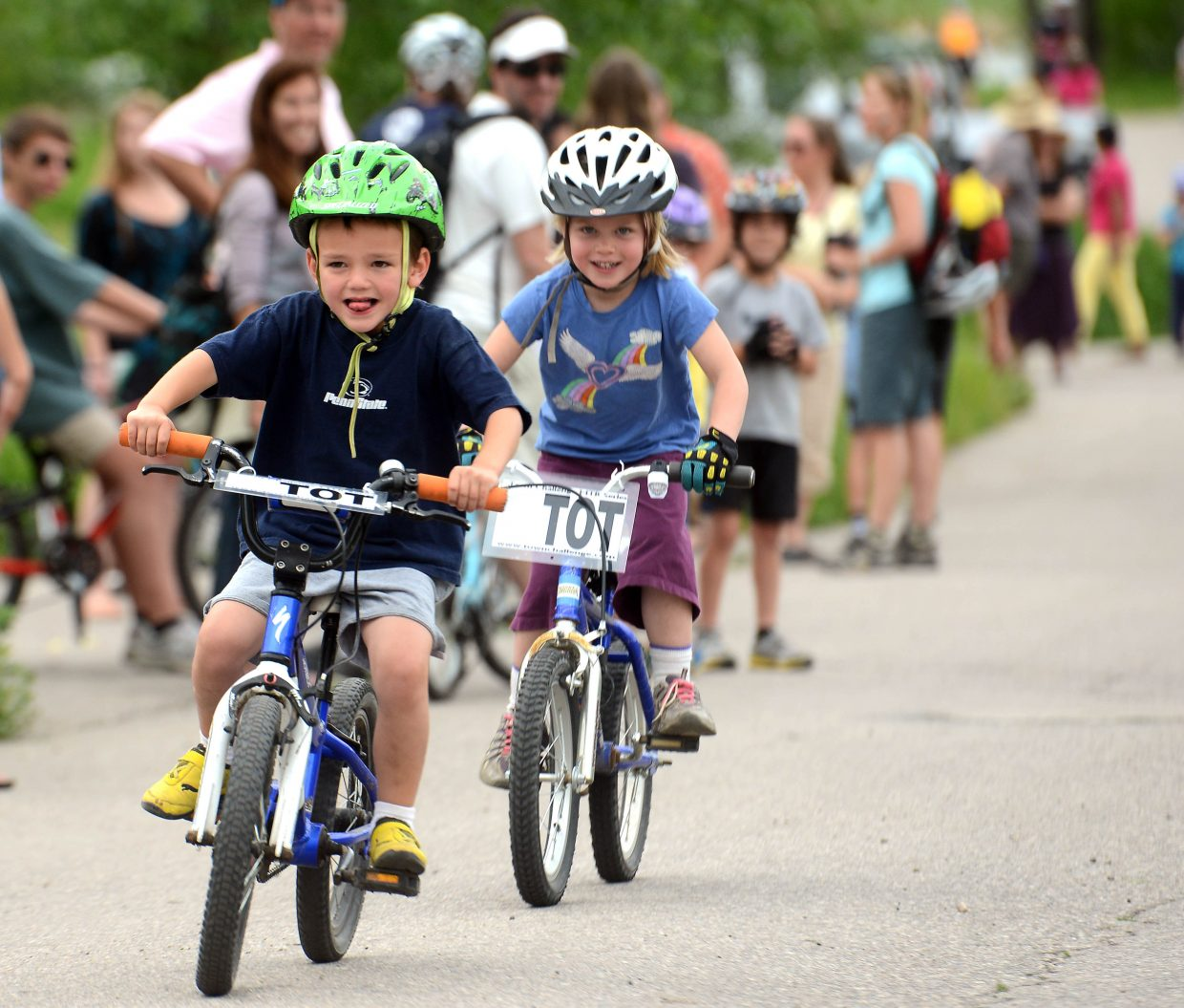 Hudson Merlina, 5, looks to his fans as he crosses the finish line during the 6-and-under race at Wednesday's Town Challenge event.