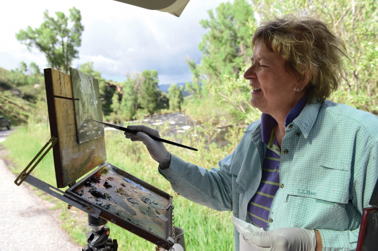 Plein Air painter Jan Sohl paints the scenery along the Yampa River Friday afternoon near Steamboat Springs. She lives in Rapid City, South Dakota, but stopped in Steamboat Springs to find the subjects for her most recent creations.