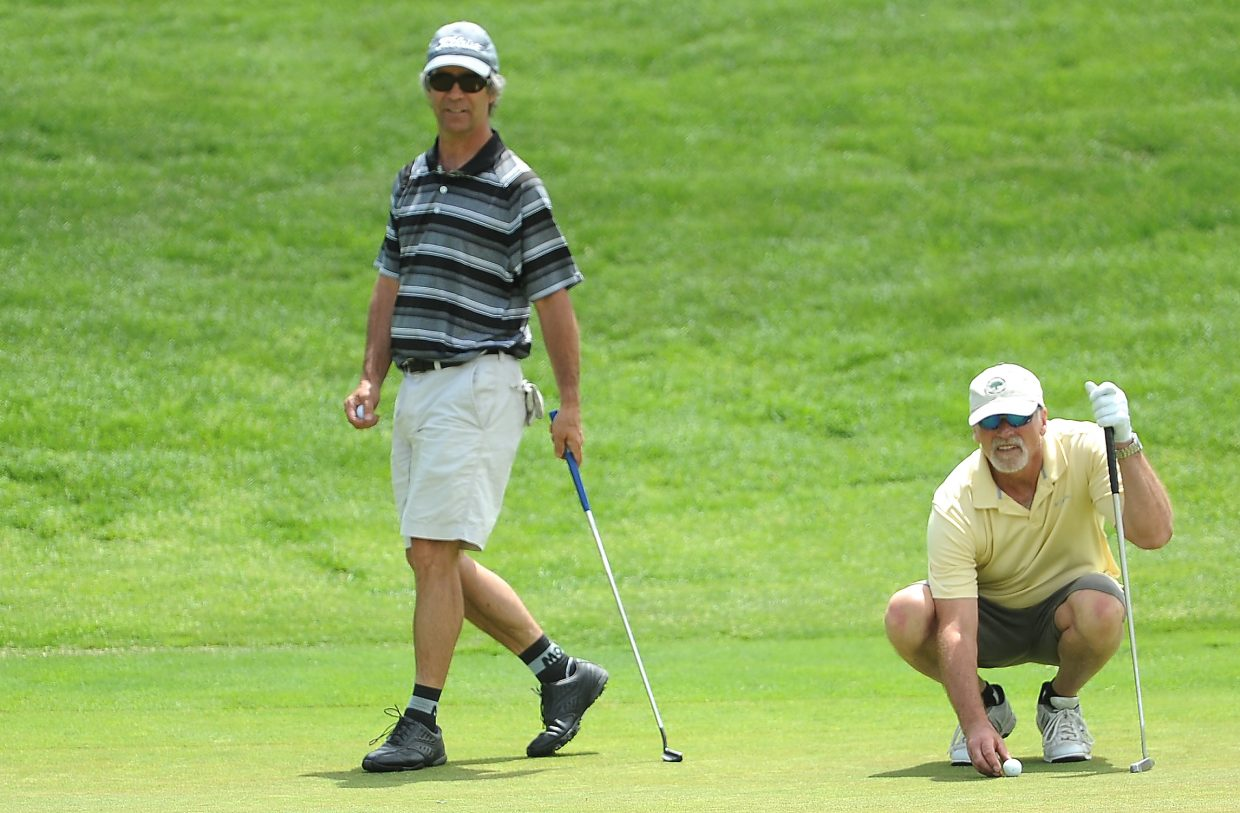 Bruce Boucher, left, and Jim Martin line up a shot Saturday during the Ski Town Classic golf tournament at Catamount Ranch & Club golf course.