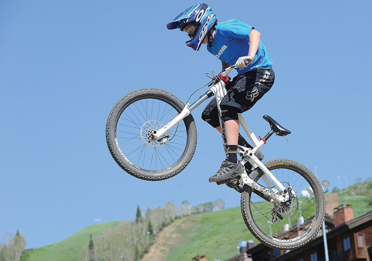 Mountain biker Sam Frackowiak hits a jump near the bottom of the Steamboat Ski Area Thursday afternoon. Frackowiak was along many cyclist who took part in scholarship day as the ski area opened the gondola to mountain bikers for the season.
