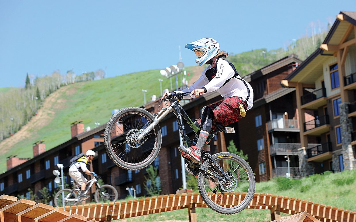 Mountain bikerss hits the jumps near the bottom of the Steamboat Ski Area Thursday afternoon. Many cyclist who took part in Scholarship Day as the ski area opened the gondola to mountain bikers in Steamboat Springs.