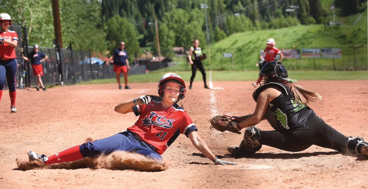 Hailey Hinson slides into home plate Friday afternoon during the Triple Crown Mountain Magic girls fast pitch softball tournament. Her team, TCS, from Fort Collins, won the contest, 5-0.