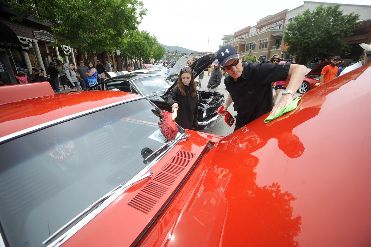 Loveland resident Todd Krauss shines up 1965 Mustang Fastback with his daughter Kristy on Saturday during the Rocky Mountain Mustang Roundup Show 'n' Shine.