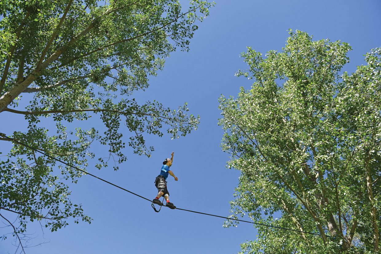 Shane Hickman makes his way across a slack line at Little Toots Park in downtown Steamboat Springs on Monday afternoon.