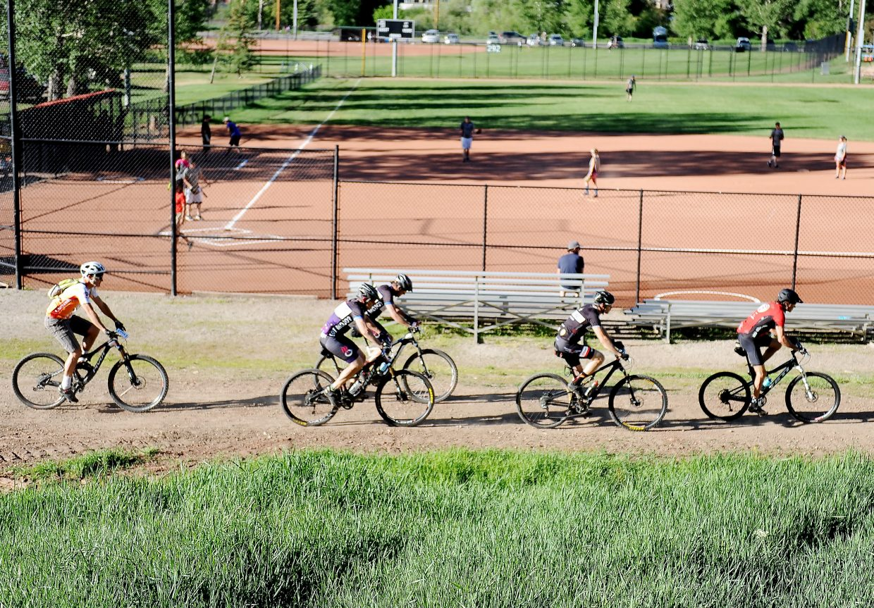 Riders in Wednesday's Town Challenge mountain bike race ride past a softball game at Howelsen Hill.