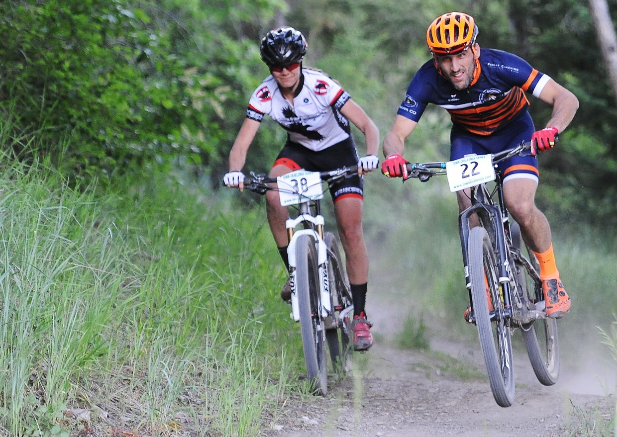 Hannah Williams, left and Jeremy MacGray race for the finish line Wednesday during the Town Challenge mountain bike race on Emerald Mountain and Howelsen Hill.