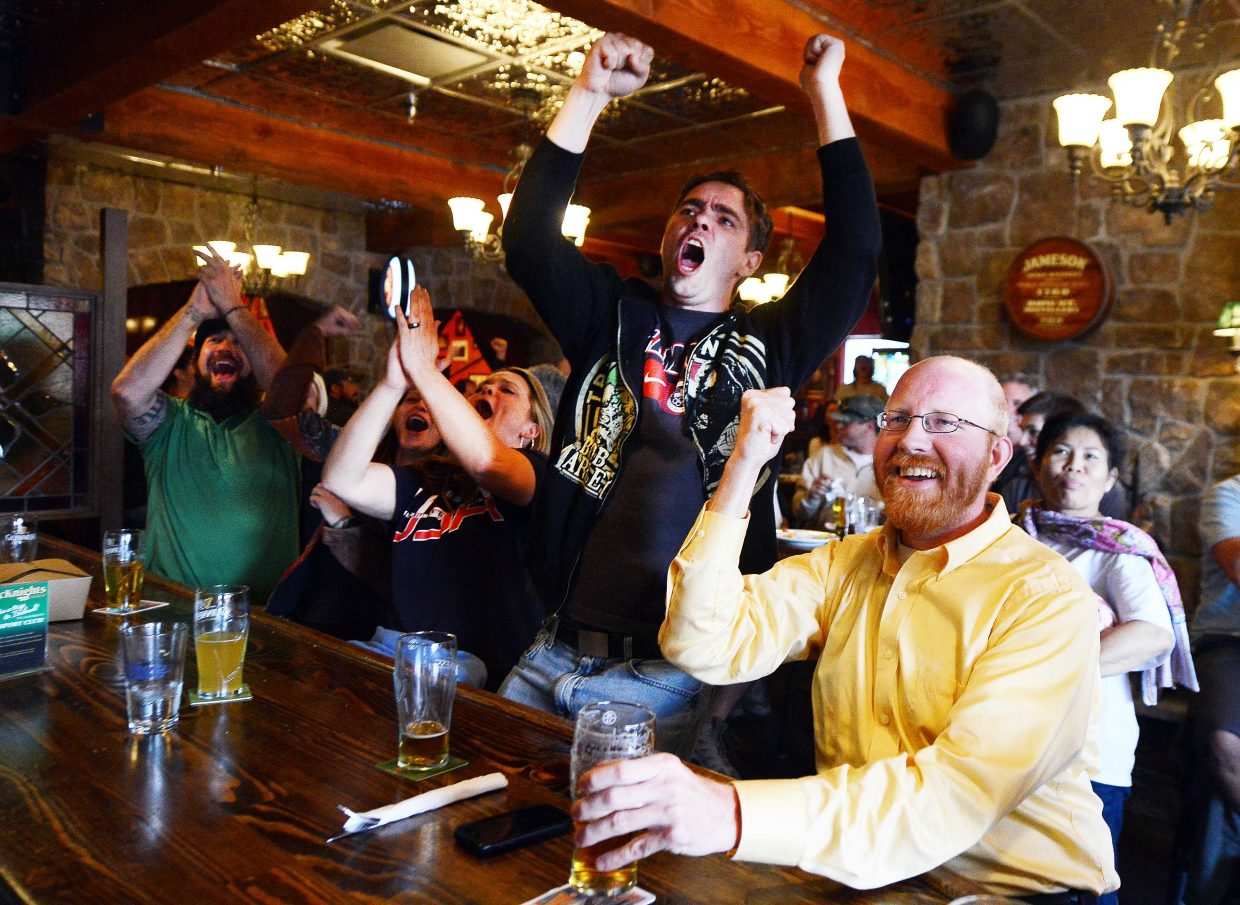 Adam Throckmorton, right, celebrates and Greg Sandruck, center, leaps out of his seat at McKnight's Irish Pub and Loft after the United States men's soccer team scored a goal in the 86th minute of the team's World Cup opening game on Monday against Ghana. Sandruck was in Steamboat with wife, Beth Sandruck, left, from Westminster, Maryland. The couple was celebrating their honeymoon in Steamboat Springs.