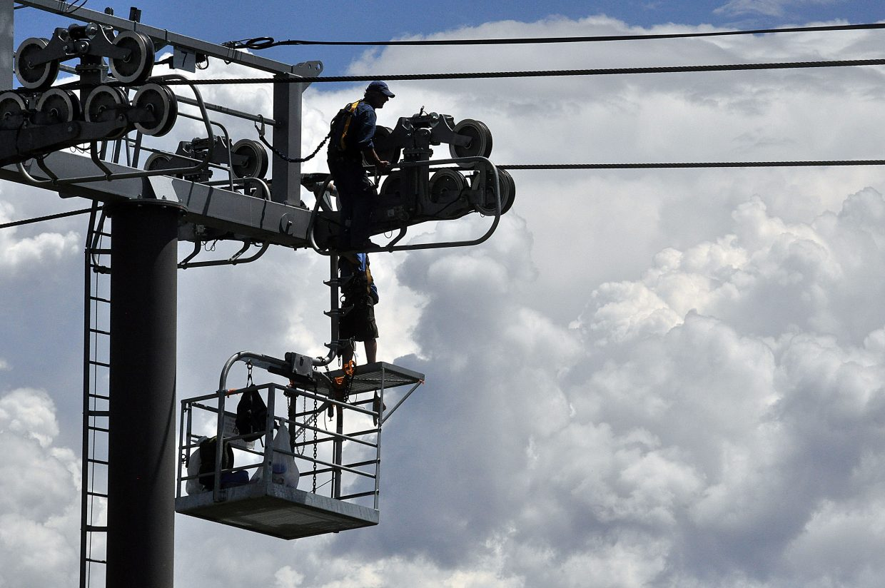 Tim McConnell, top, and Jesse Draper perform maintenance on the Wildhorse Meadows Gondola on Wednesday afternoon.