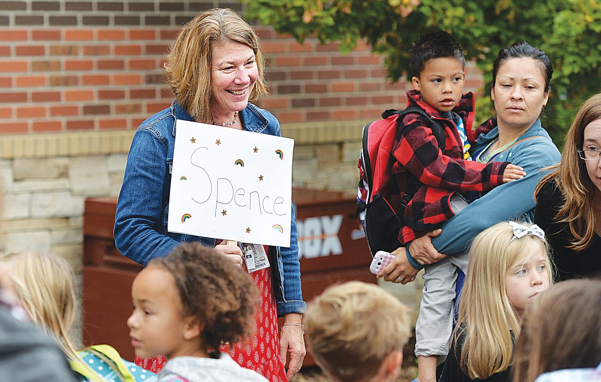 Kindergarten teacher Kristi Spence holds a sign showing her new students where to line up on the first day of kindergarten in 2015.