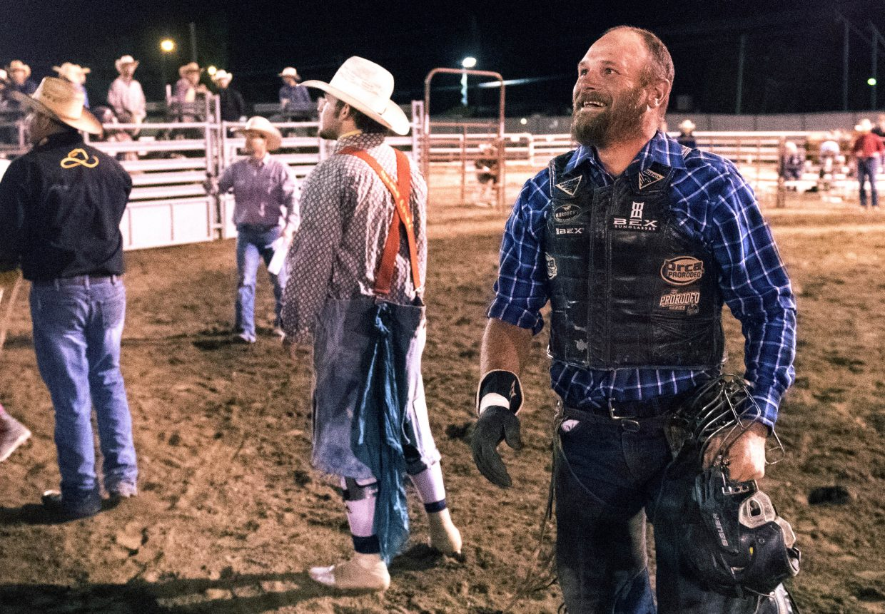 Hayden's Chad Day smiles wide as he exits the Routt County Fair rodeo arena in Hayden after falling just short of the eight-second ride he needed in Thursday night's bull riding competition.