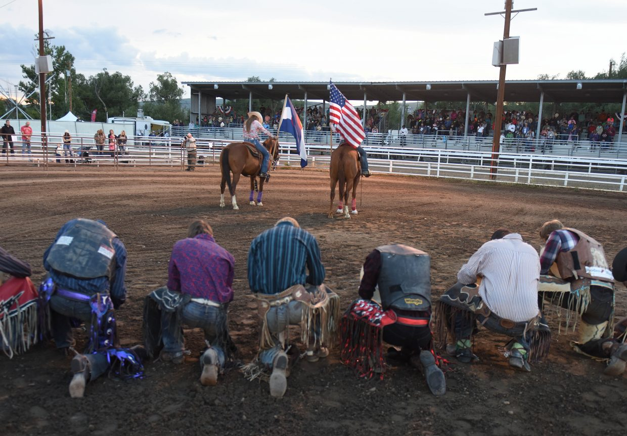 Thursday's bull riders take a knee during the cowboy's prayer at the Jake Booco Invitational Bull Riding, a part of the Routt County Fair in Hayden.