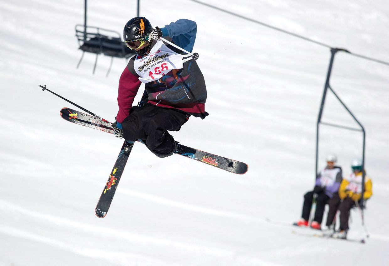 Freestyle skier Chase Mohrman flies high from the Mavericks superpipe at Steamboat Ski Area as his fellow competitors watch from the chairlift in Bashor Bowl during the 2011 Freestyle Junior Nationals.