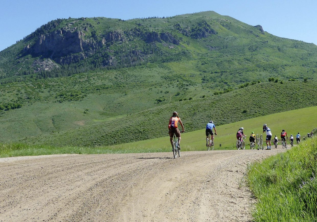 Cyclists ride by Sleeping Giant during Saturday's Moots Ranch Rally.
