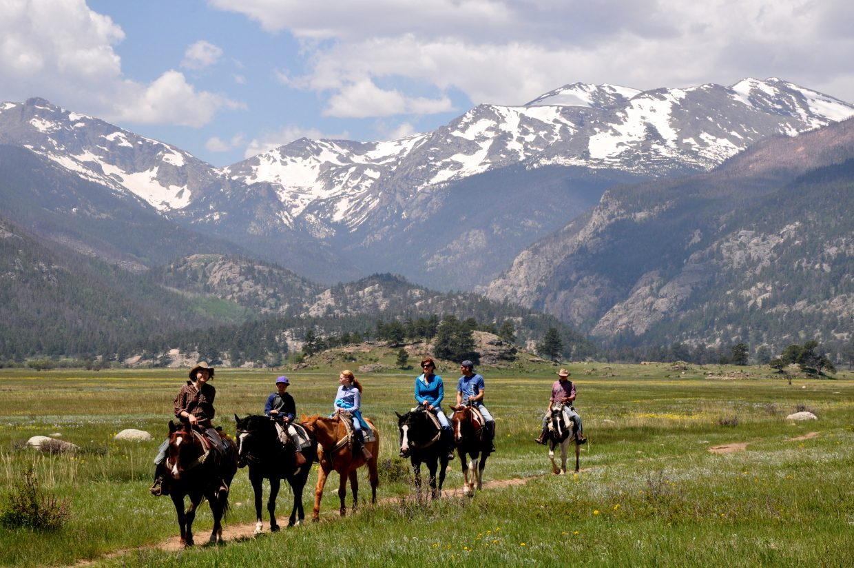 Horseback riders take in the view on a trail in Rocky Mountain National Park.