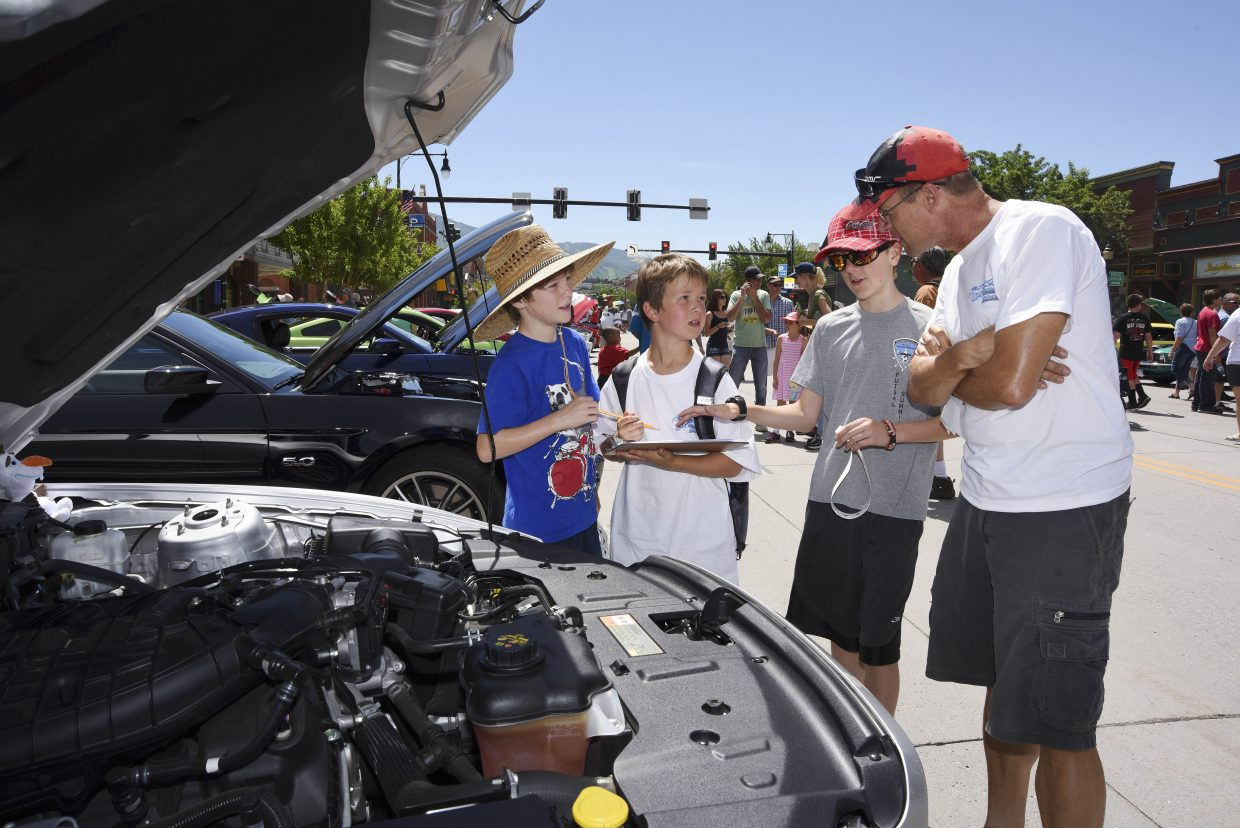 Judges, from left, Jaydon Fryer, Chili Craigen, Jaxson Fryer and Robin Craigen critique a Mustang during the Mustang Roundup Show N' Shine on Saturday in downtown Steamboat Springs.