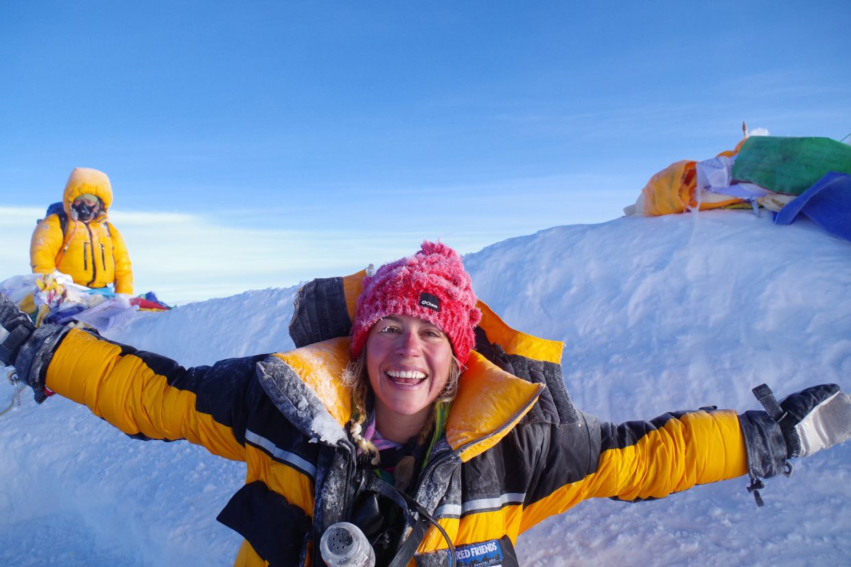 Kim Hess throw her arms out from the summit of Mount Everest.