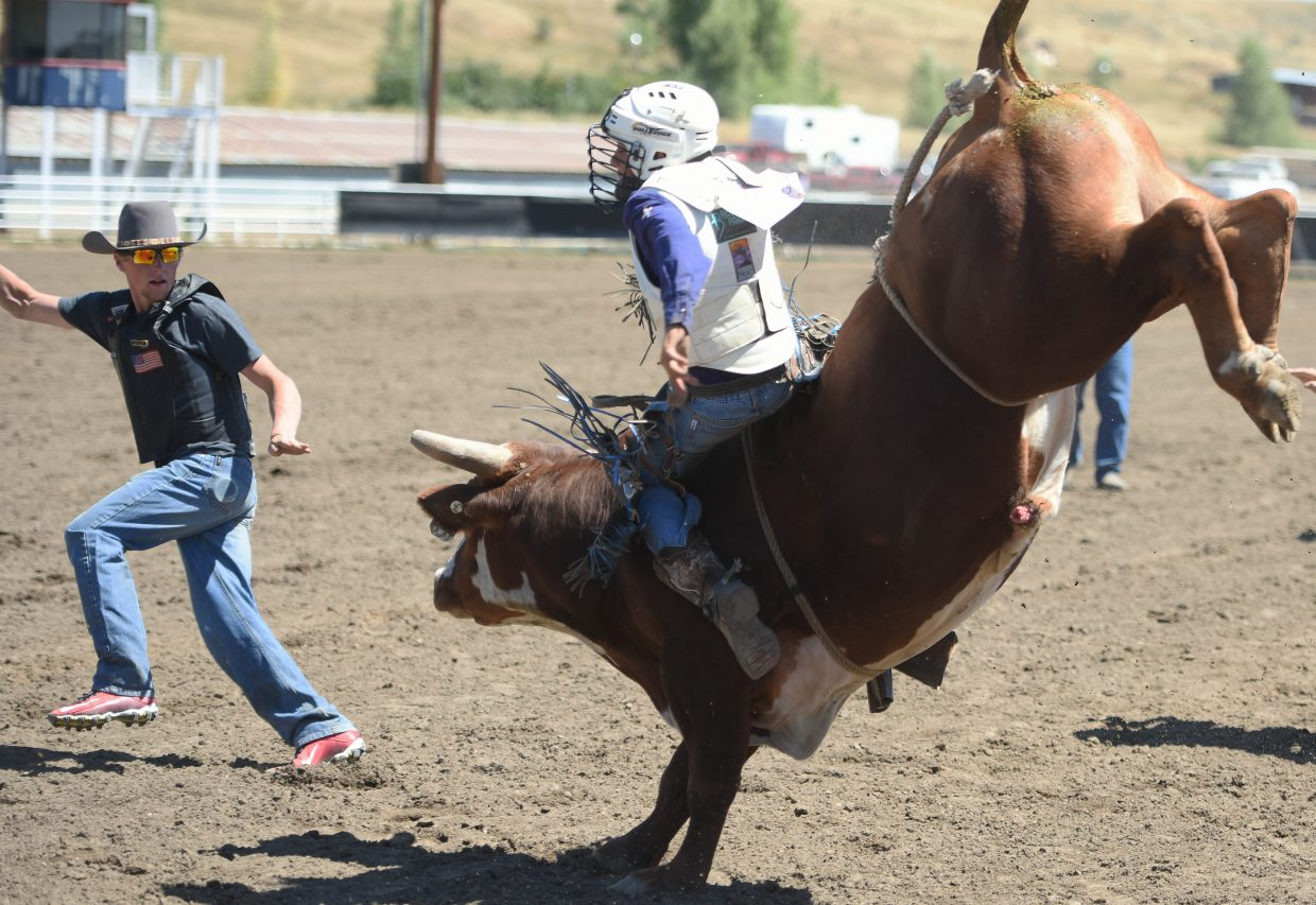 Ezra Wagner hangs on as his bull launches into the ring Sunday during the Lil' Buckaroo Junior Rodeo at the Routt County Fair in Hayden.