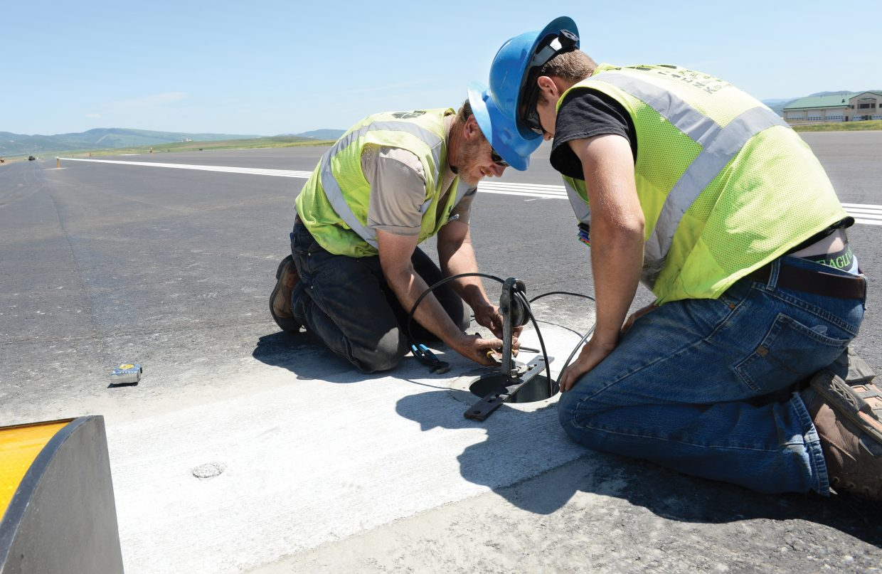 Electrical workers Shane Lance and his son Ethan install new lights along the runway at Yampa Valley Regional Airport Monday afternoon. Planes will be landing on wider, recently reconstructed runway when the airport reopens for business Thursday afternoon. Weather problems caused delays with the repaving project earlier this spring, but once things dried out, crews stayed busy to get the project finished in time for the busy summer season — just a little more than a week after the project was expected to have been completed.