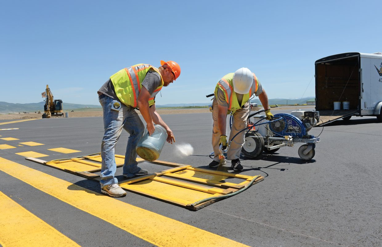 Jake Adams, left, and Brandon Fink of Straight Stripe Painting complete a few of the finishing touches at the Yampa Valley Regional Airport on Monday afternoon. The airport, which has been shut down as part of a large repaving project, is expected to reopen Thursday with the first commercial flights coming in that evening.
