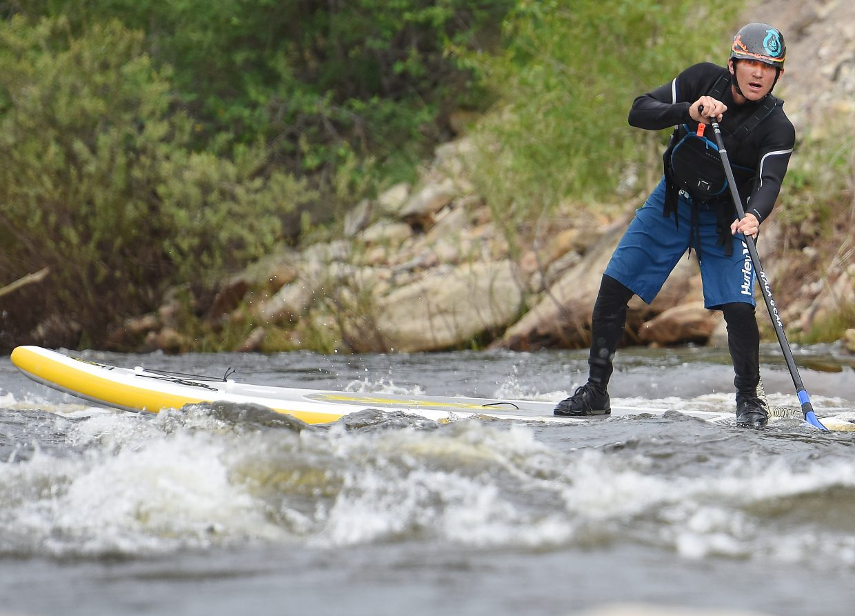 Danny Tebbenkamp, owner of Steamboat Paddleboard Adventures, spins his stand-up paddleboard and eyes Charlie's Hole on the Yampa River in downtown Steamboat Springs on Wednesday afternoon as the river raged late in the melting season.