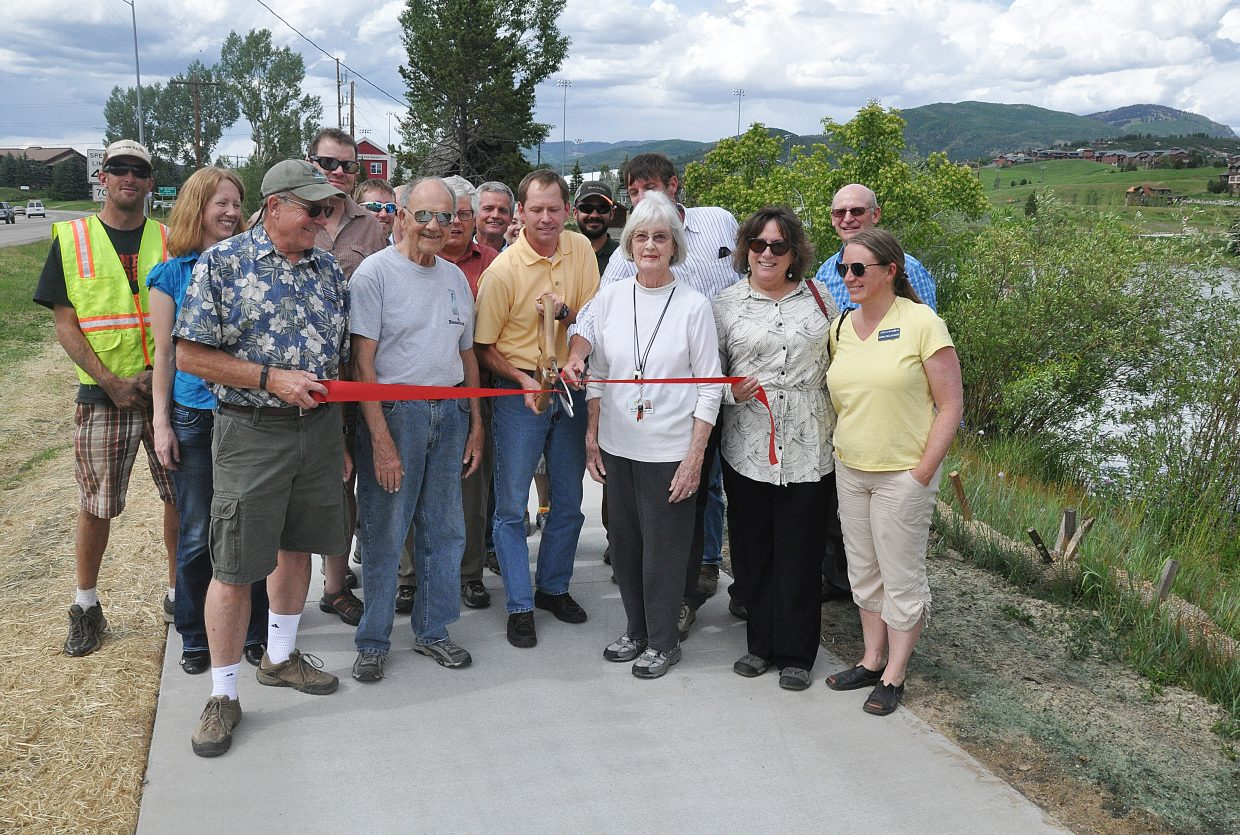 Steamboat Springs City Council President Bart Kounovsky cuts the ribbon on the new Casey's Pond trail as other city officials and some trail users look on. The trail connects the Walton Creek corridor to areas along Pine Grove Road. The city project added 400 linear feet of concrete trail along Walton Creek Road and replaced a degraded asphalt trail along U.S. Highway 40 with a concrete trail, making the area safer for pedestrians and bikers. The project was completed on time and under budget.