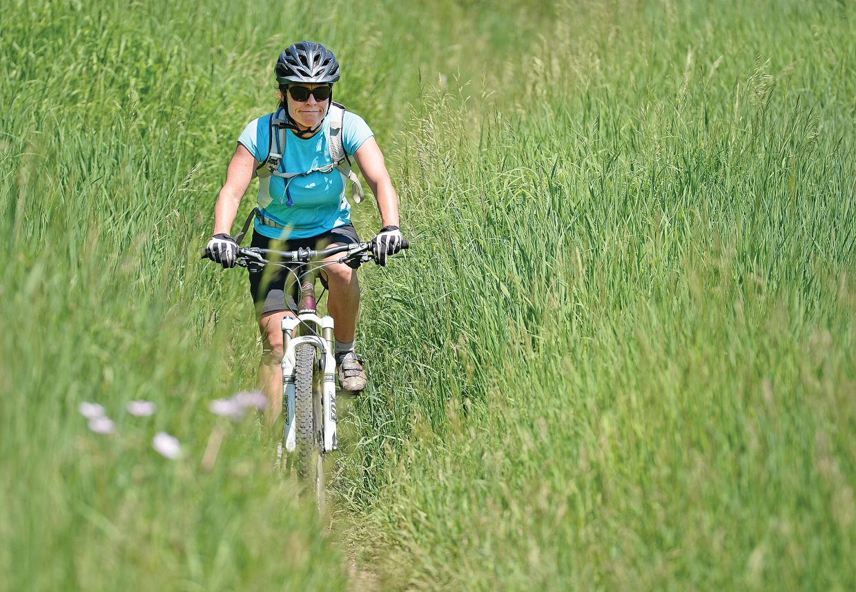 Steamboat Springs Monica Niedermeier rides her bike through the tall grass on a trail behind the Steamboat Springs Middle School Tuesday afternoon.