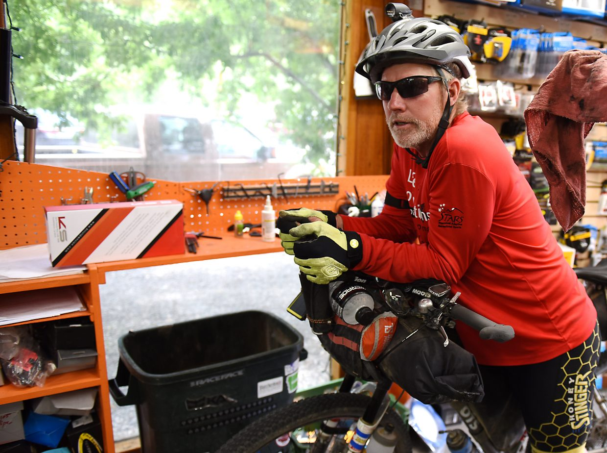 Mike Schlichtman rests on his bike after pulling into Orange Peel Bike Service in Steamboat Springs. Schlichtman is riding the Tour Divide, a 2,745 mountain bike race that runs from Canada to the United States-Mexico border.