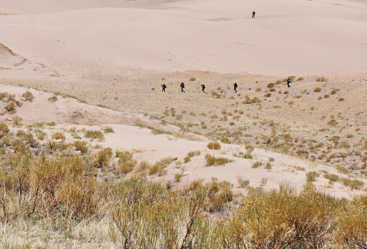 A group of backpackers start the trip on the Sand Ramp Trail. The trail traverses an area where the vast dune field meets the foothills of the mountains.