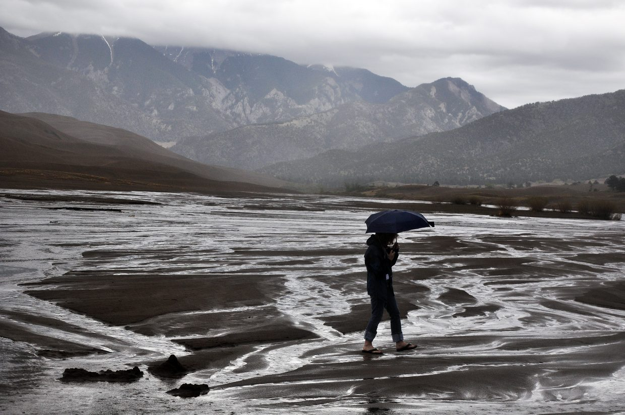 Rain doesn't stop activity at the Great Sand Dunes. A woman walks on Medano Creek as rain storms pass through the area.