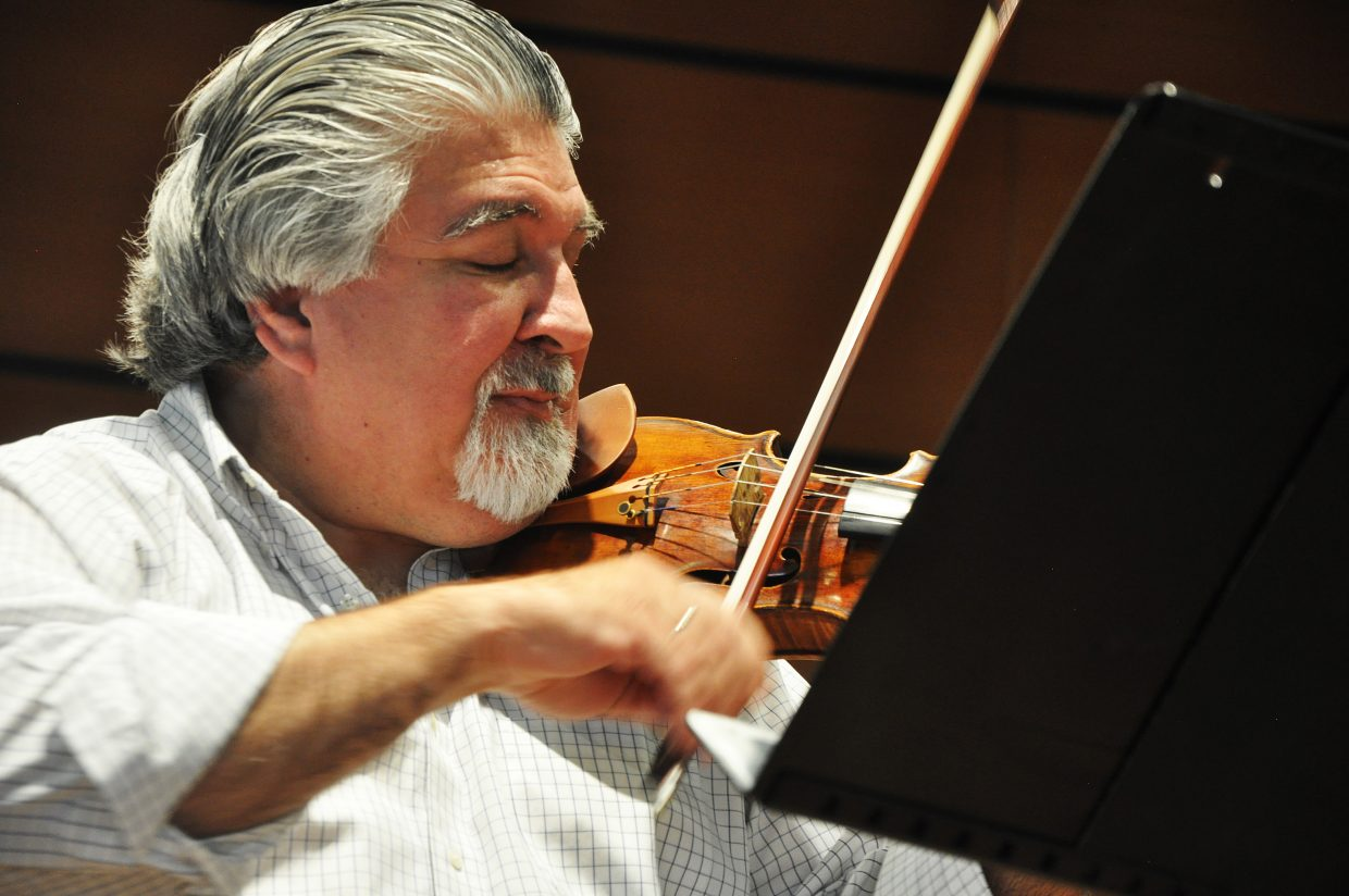 Conductor Andres Cardenas plays the violin during a rehearsal for an upcoming classical show at Strings.