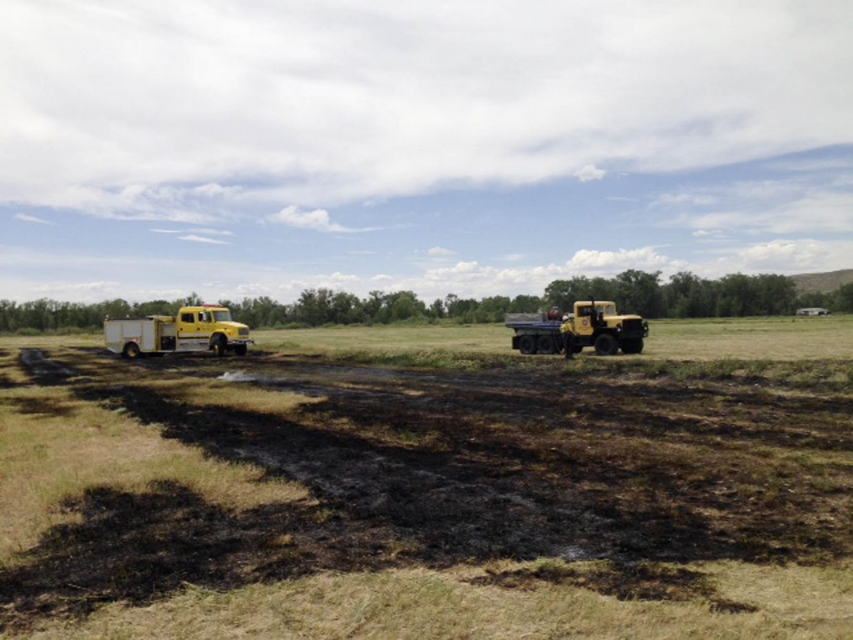West Routt Fire Protection District firefighters work at a hay field fire Thursday about 2 miles from Hayden in the Breeze Basin area.