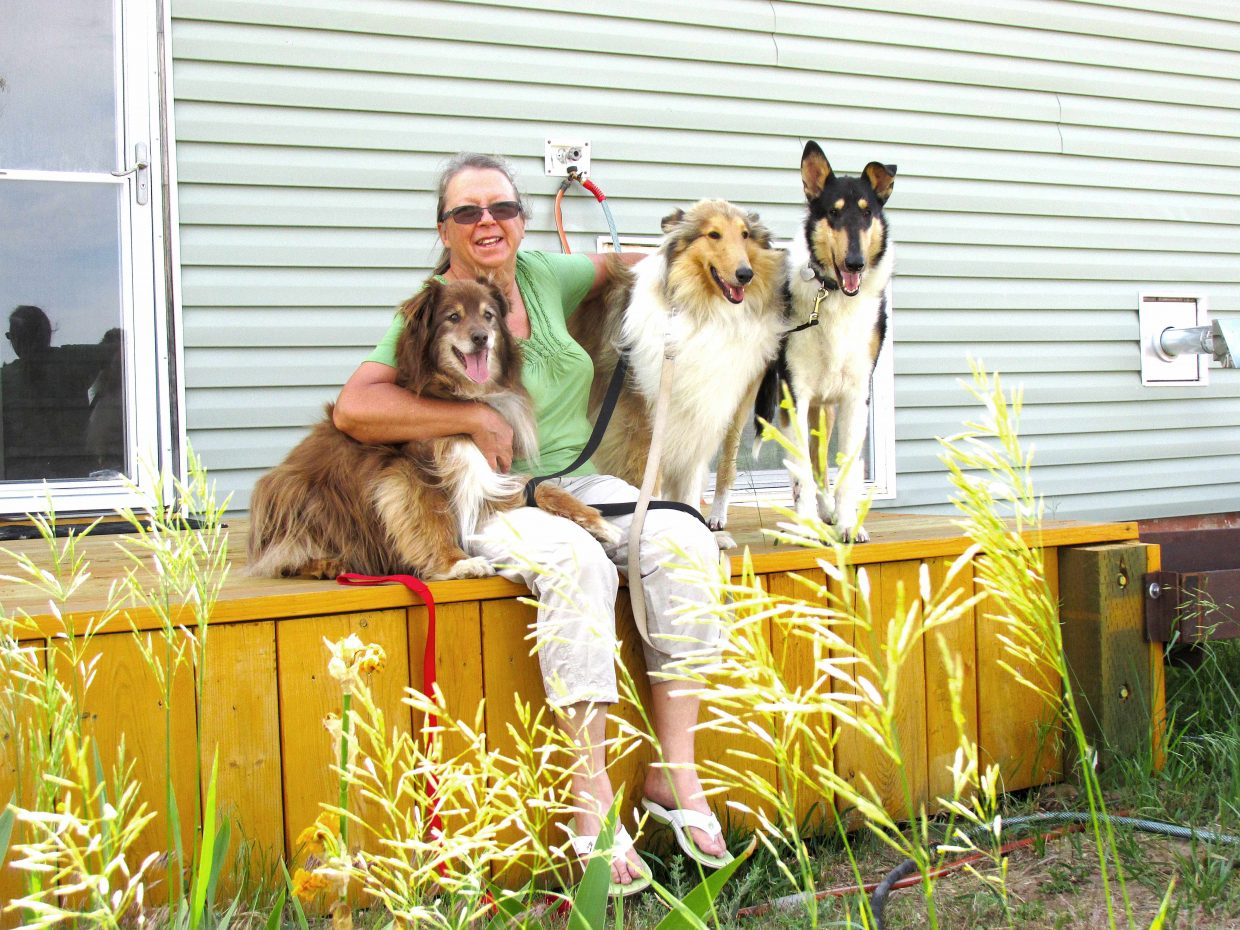 Copper, left, Trish Foster, Cora and Corky pose together at Foster's Craig home. Foster rescued Cora and Corky from Texas.