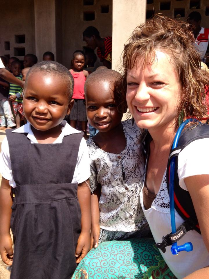 Grace Hampton smiles with two little kids from the small town of Zambo near Malawi, Africa.