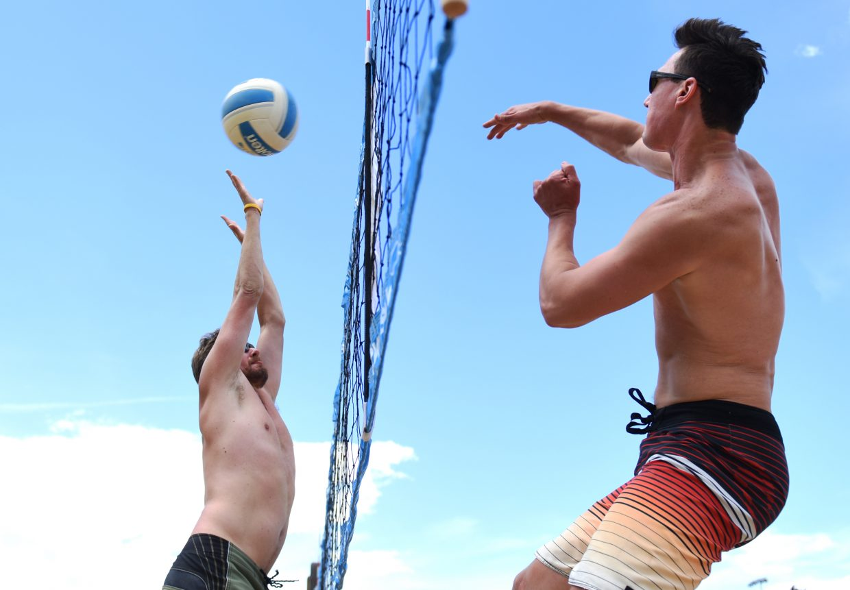 Ryan Post, left, reaches high for a kill off the hand of Dave Maitlen on Friday during a match in the dinosaur division of the Steamboat Doubles Volleyball Tournament. Play continues in the tournament Saturday and Sunday at the base of Howelsen Hill.