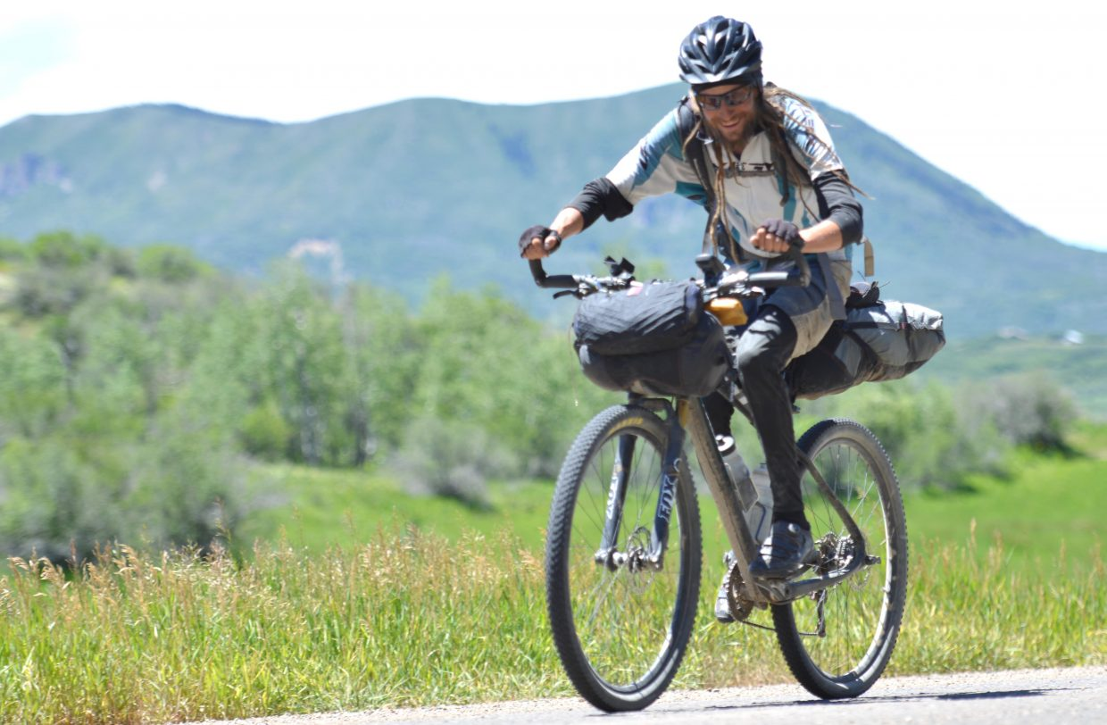 John Fairbairn rides toward Steamboat Springs on Monday while competing in the Tour Divide mountain bike race. Fairbairn, who lives near Stagecoach, said the ride has been difficult but rewarding so far.
