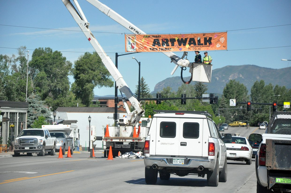 City of Steamboat Springs public works employees Gus Trujillo, left, and Dave Burton descend in a bucket truck after putting up a banner advertising Steamboat's First Friday Artwalk. The city of Steamboat Springs is projecting a 4 percent growth in sales tax next year.