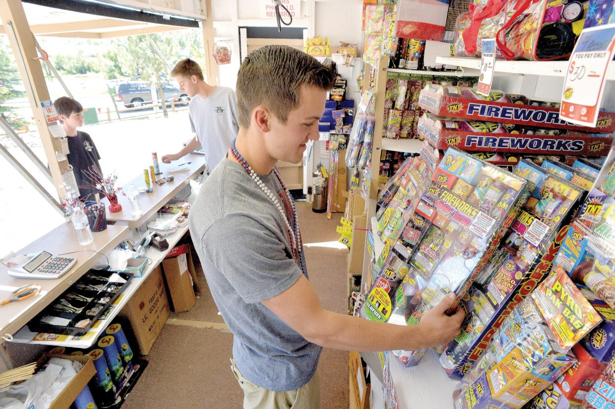 Employees Charles Toye, front, and Grant Birkenbine help customers at the TNT Fireworks stand on the west side of Steamboat Springs. Despite the fact that there are no fire restrictions, stand owner Mary Dike always cautions her customers to be safe when setting off fireworks in the Steamboat Springs area.