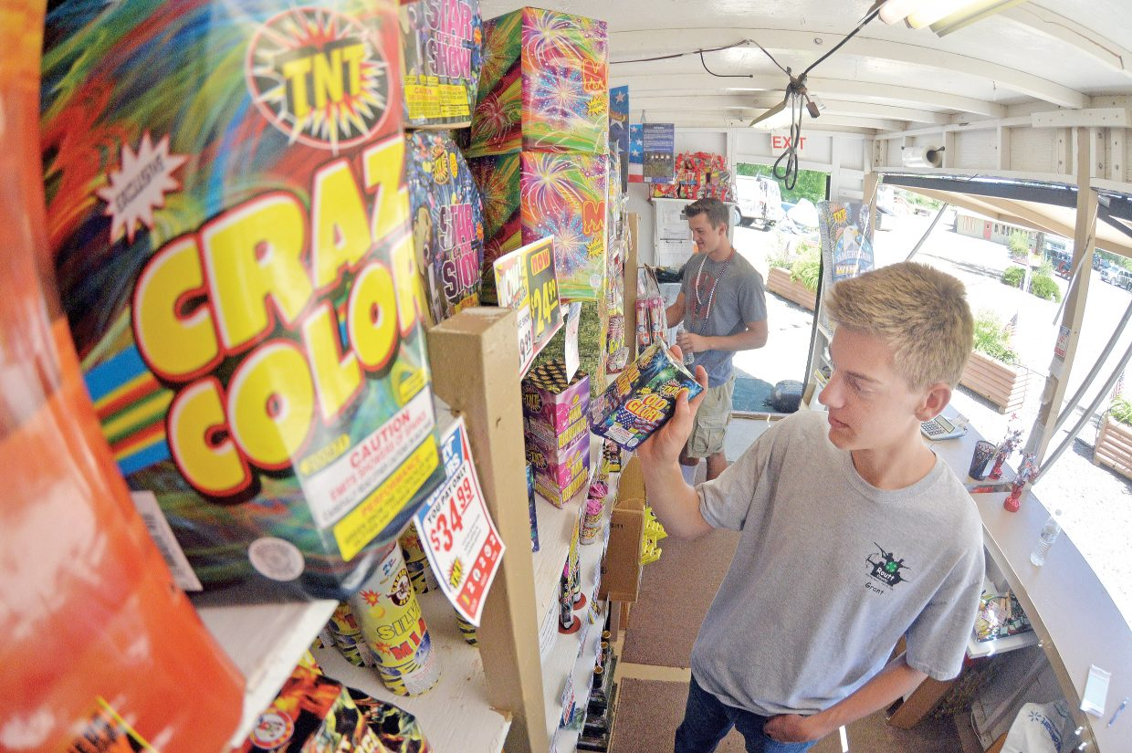 Employees Grant Birkenbine, front, and Charles Toye help customers at the TNT Fireworks stand on the west side of Steamboat Springs.