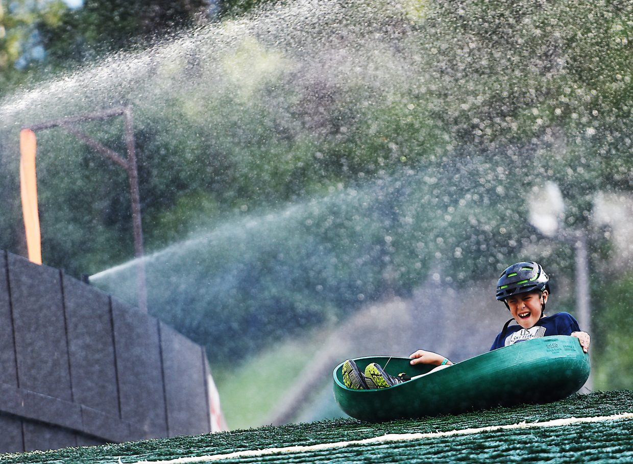 Reid Sias flies through the sprinklers and down the slope on the HS45 landing hill at Howelsen Hill in Steamboat Springs. The Steamboat Springs Winter Sports Club will start offering people the chance to take that ride, calling it the Nordic Screamer, on Sunday.