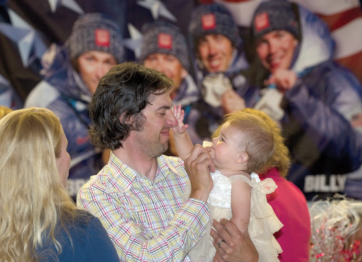 Spillane plays with his daughter Genevieve while visiting with guests at his retirement party in July at Olympian Hall.