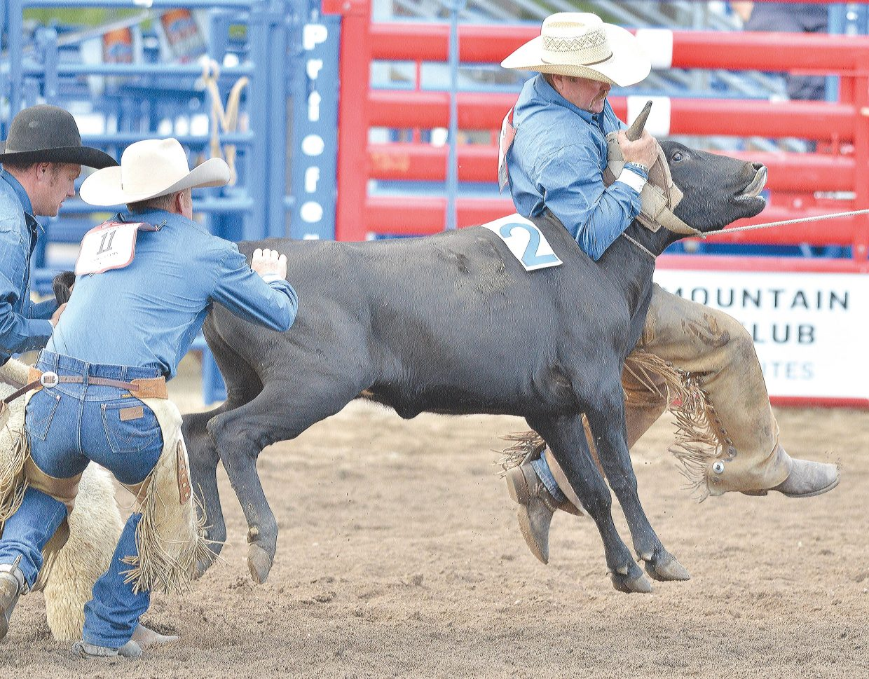 Frank Thompson and his teammates with the Four Three Land and Cattle/FX Bar team wrestles an uncooperative steer during Thursday night's Working Ranch Cowboys Association-sanctioned ranch rodeo at the Brent Romick Rodeo Arena. Ten professional teams competed in the event and entertained a good-sized crowd in an event that kicked off the Fourth of July celebration in Steamboat Springs.