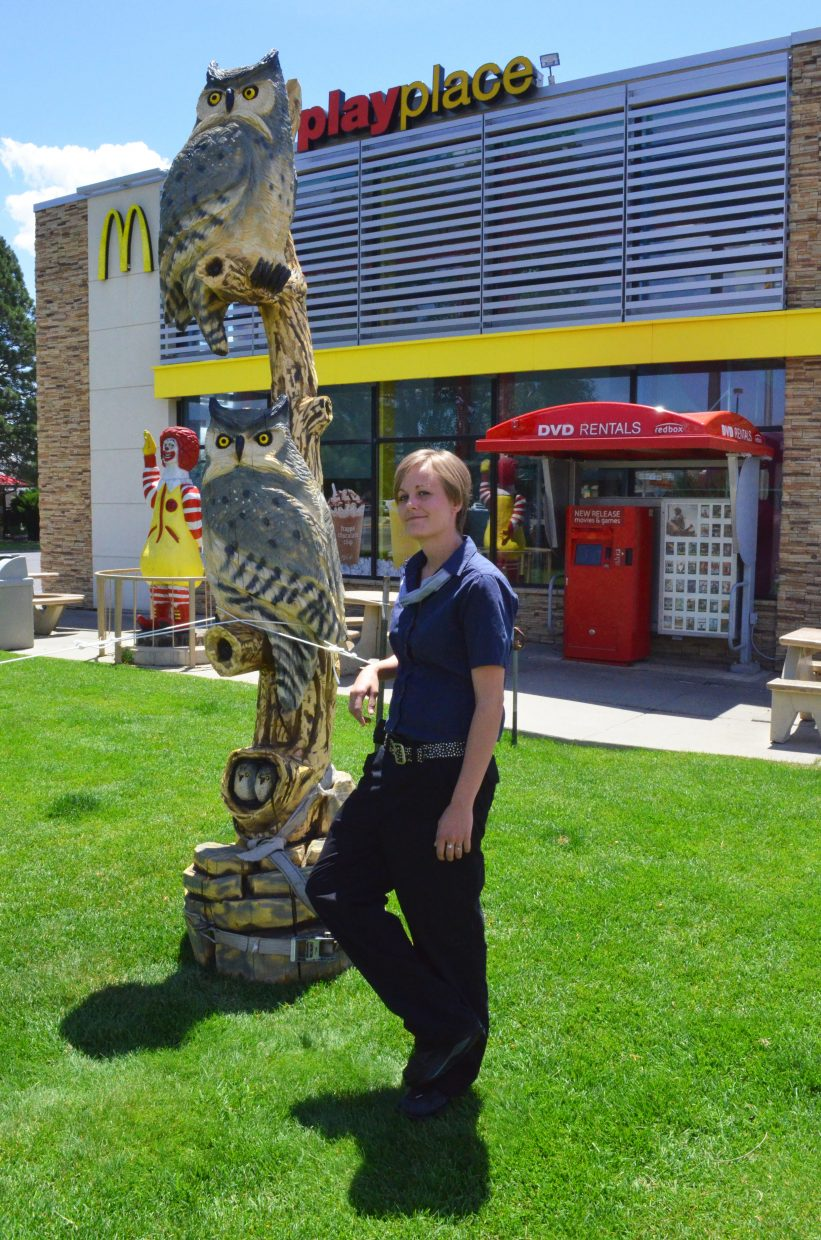 """Emily Knudsen, general manager for the Craig McDonald's, welcomes the newest addition to the fast food restaurant's lawn, the owl piece, """"Big Hooters."""" The winner of this year's Whittle the Wood Rendezvous was recently placed on the businesses property, as were other carvings in spots around Northwest Colorado."""