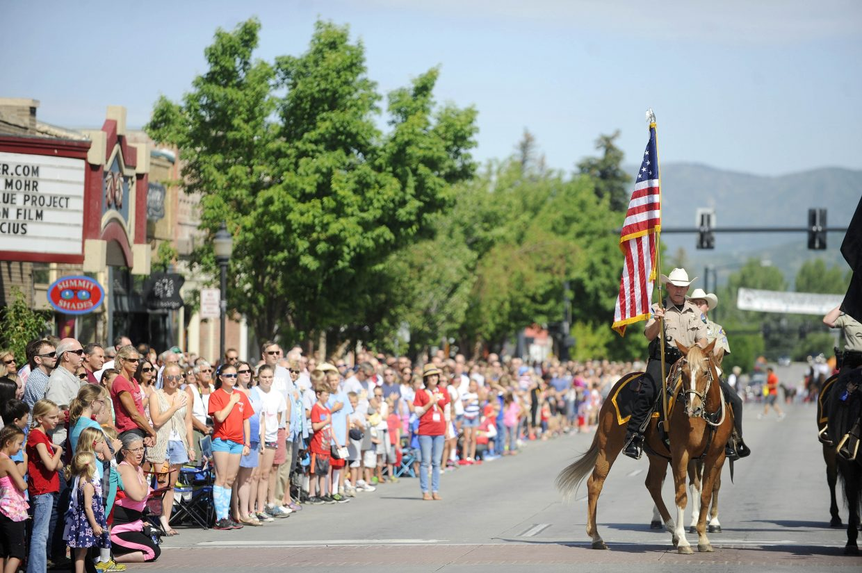 """Routt County Undersheriff Ray Birch displays the American Flag during singing of """"Star Bangled Banner"""" on Friday during the Fourth of July parade in Steamboat Springs."""
