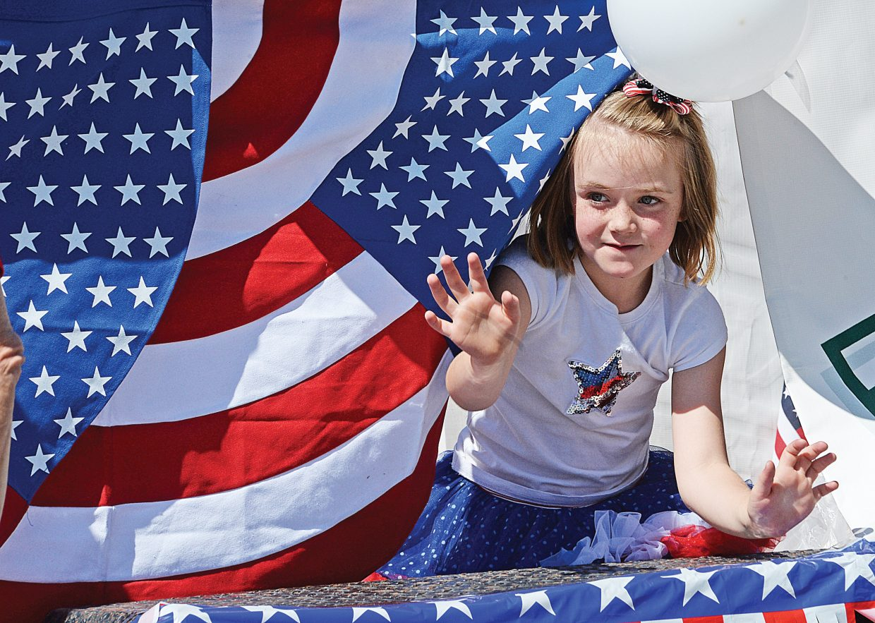 Clover Fisher peeks out from behind the red, white and blue of a float Monday morning to wave at the crowd that gathered for the Yampa Valley Bank Fourth of July Parade in downtown Steamboat Springs.