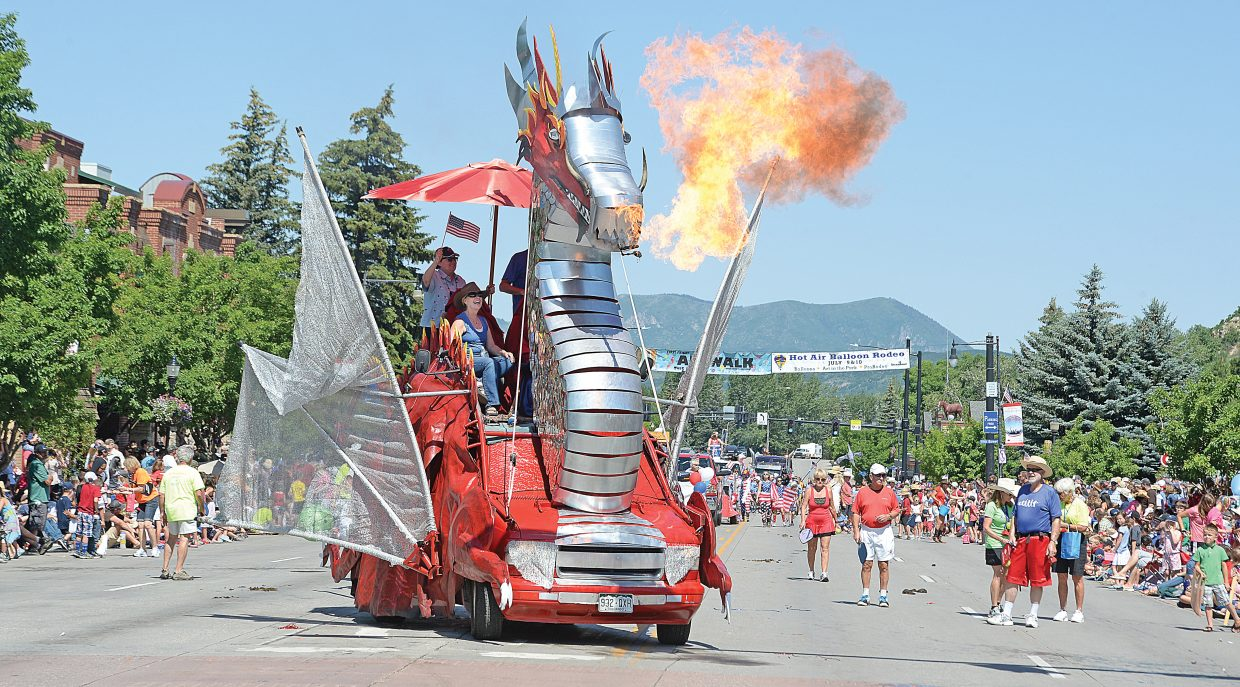 Phoenix Dragon of Fire lets loose with a ball of fire as owners Gail and Charley Holthausen drive the art car down Lincoln Avenue as part of the Yampa Valley Bank Fourth of July Parade.