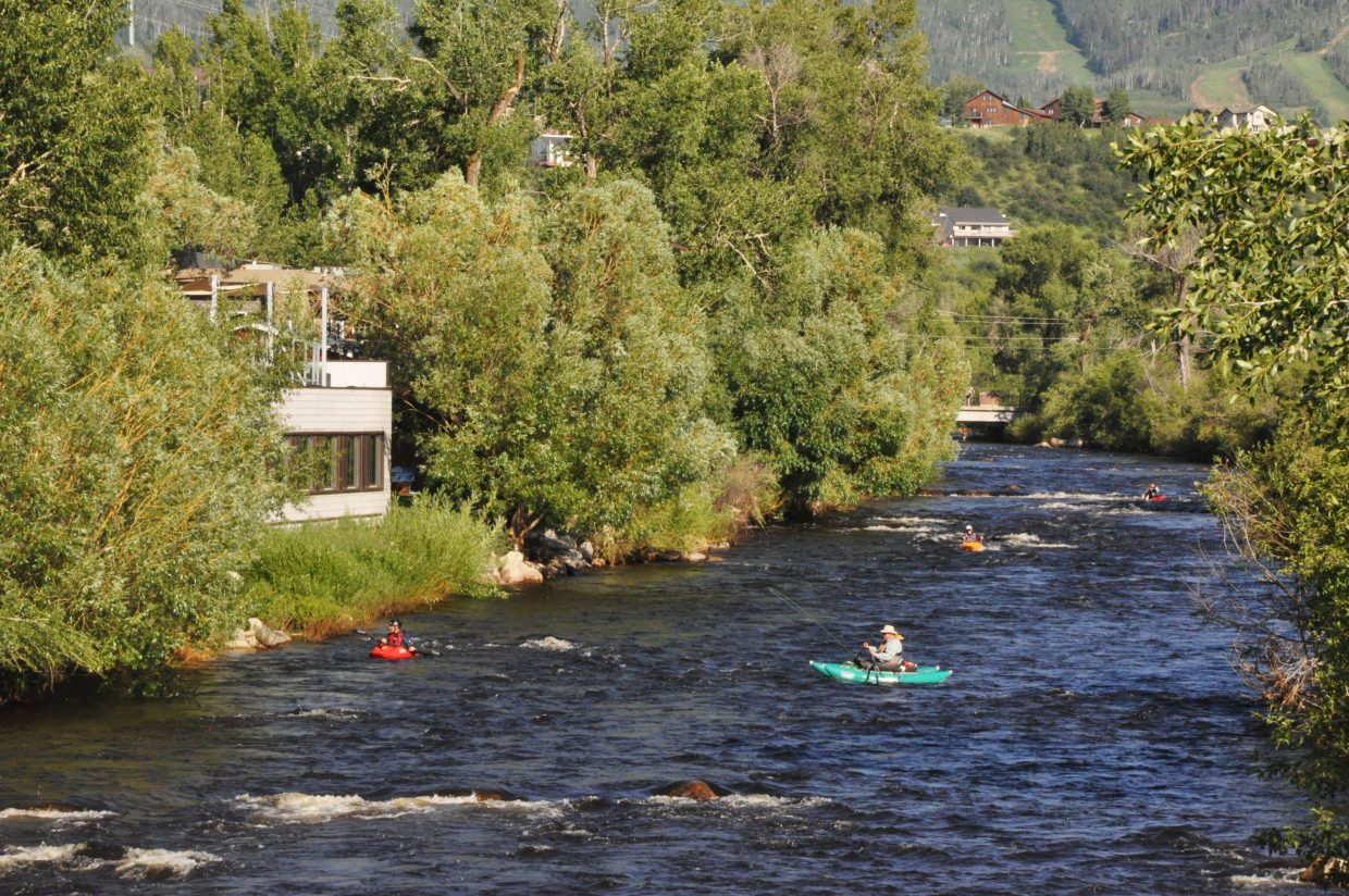 Kayakers and pontoon boats float by the Yampa River just outside of Aurum Food and Wine. This property used to be the home of a successful fish hatchery.