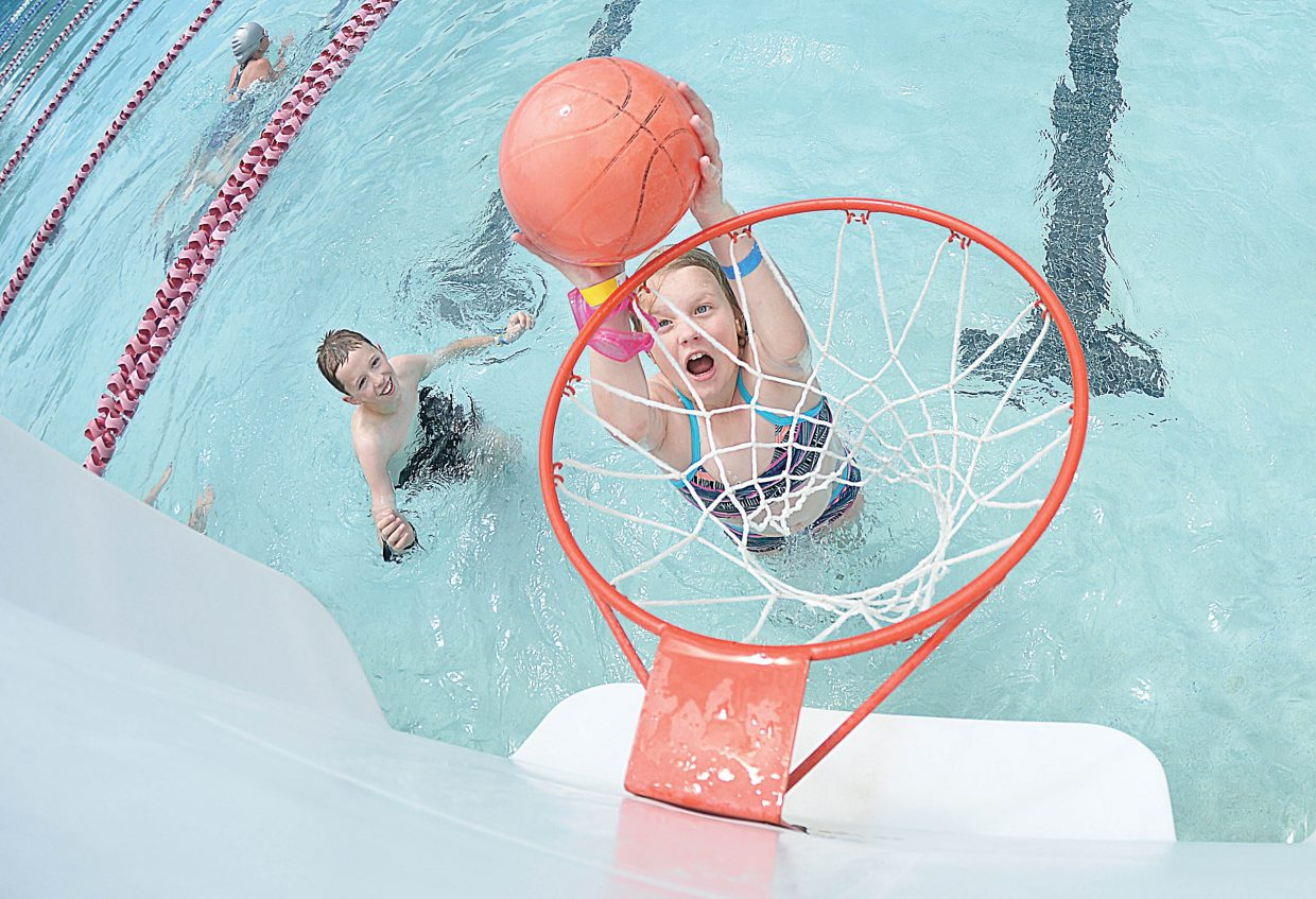 McKenzie Clark goes for the dunk while playing basketball with Brandon Walker at the Old Town Hot Springs Pool Monday afternoon. The two were visiting Steamboat Springs from Yampa.