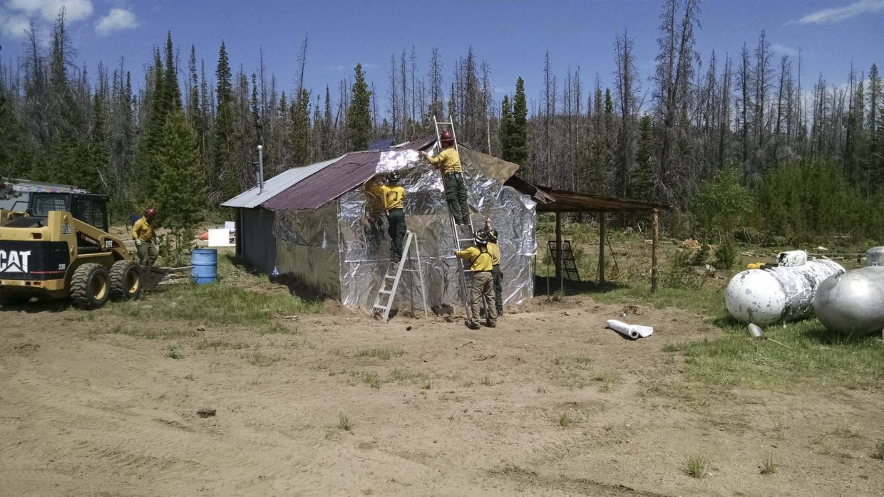 A cabin is wrapped to protect it from the Beaver Creek Fire.